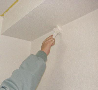 天井の見切り部分をハケで2回目の塗装をする
